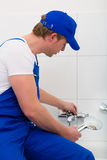 Plumber repairing shower in bath room Stock Photos