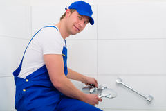 Plumber repairing shower in bath room Royalty Free Stock Images