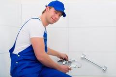 Plumber repairing shower in bath room Royalty Free Stock Images