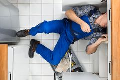 Plumber repairing sink. High Angle View Of A Plumber Repairing Sink In Kitchen Stock Photos