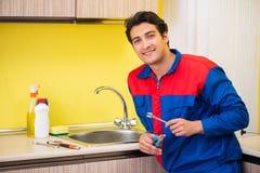 Plumber repairing tap at kitchen stock image