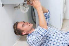 Plumber repairing washbasin drain in bathroom Royalty Free Stock Photo