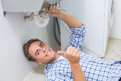 Plumber repairing washbasin drain while gesturing thumbs up. Portrait of a young plumber repairing washbasin drain while gesturing thumbs up in bathroom Royalty Free Stock Images