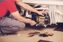The plumber repairs the pipes. Male specialist plumber repairs. royalty free stock images