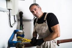 Plumber repairing metallic water pipes with manometer royalty free stock image