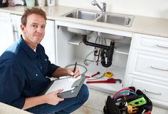 Plumber. Residential plumber doing renovation in kitchen home Royalty Free Stock Photography