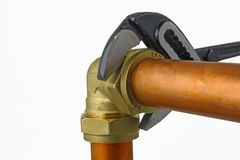 Plumber`s adjustable wrench tightening up copper pipework. An adjustable wrench tightening up a compression elbow fitting to 15mm copper pipework on a white stock image
