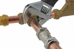 Plumber`s adjustable wrench tightening up copper pipework. An adjustable wrench tightening up a compression tee fitting to 15mm copper pipework on a white royalty free stock photo