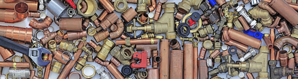 Plumber`s pipes and fittings website banner. Wide random mixture of copper pipe and brass fittings ideal for use as a website header background Royalty Free Stock Photos