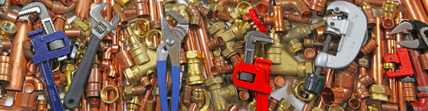 Plumber`s pipes , fittings and wrenches  website banner. Wide  random mixture of copper pipe, brass fittings  and wrenches ideal for use as a website header Royalty Free Stock Image