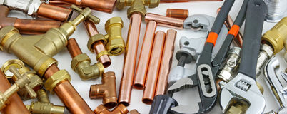Plumber`s pipes , fittings and wrenches  website banner. Wide  random mixture of copper pipe, brass fittings  and wrenches ideal for use as a website header Royalty Free Stock Photos
