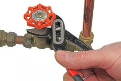 Free Plumber`s Wrench Tightening Up A Valve Royalty Free Stock Photo - 99718625