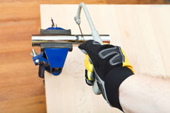 Plumber sawing plumbing drain pipe gripped in vice. On wooden table by hacksaw Royalty Free Stock Image