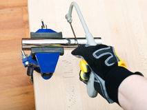 Plumber saws metal trap pipe gripped in vice Royalty Free Stock Photo