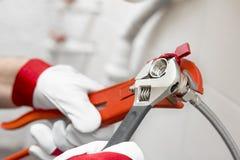 Plumber screwing plumbing fittings in bathroom Stock Images