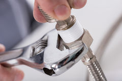 Plumber screwing plumbing fittings. Closeup Stock Photo
