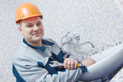 Plumber service. worker installing mixer tap in bathroom Stock Images