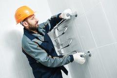 Plumber service. worker installing towel warmer. Plumbering service. plumber worker installing towel warmer Stock Photos