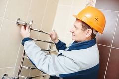 Plumber service. worker installing towel warmer. Plumbering service. plumber worker installing towel warmer Royalty Free Stock Photos