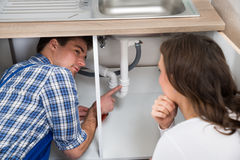 Plumber Showing Damage In Sink Pipe To Woman Royalty Free Stock Photos