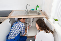 Plumber Showing Damage In Sink Pipe To Woman Stock Photography