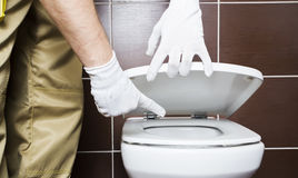 Plumber showing problem area of toilet Stock Photos
