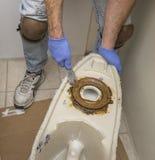 Plumber showing wax ring on toilet base Royalty Free Stock Image