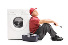 Plumber sitting by a washing machine and thinking Royalty Free Stock Image