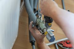 Plumber squeezes plastic pipes for a new installation royalty free stock photography