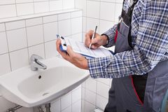 Plumber standing in front of washbasin writing on clipboard Royalty Free Stock Photos