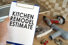 Plumber taking clipboard with kitchen remodel estimate. Plumber holding clipboard with kitchen remodel estimate stock image