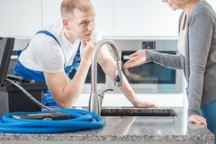 Plumber talking to client. Focused plumber talking to a client over a sink in a kitchen Stock Photos