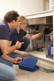 Plumber Teaching Apprentice To Fix Kitchen Sink royalty free stock image
