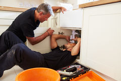 Plumber teaching an apprentice to fix a kitchen sink stock images