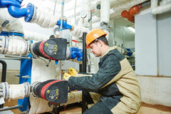 Plumber technician works with water pump. Plumber work. Construction worker installing water high pressure pump meter in boiler room royalty free stock photos