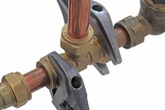 Plumber tightening up pipework thats leaking. Two adjustable wrenches tightening up tee-fitting on 15mm copper pipework isolated on a white background royalty free stock photo