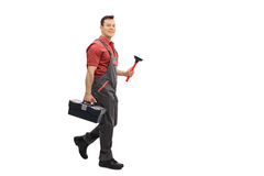 Plumber with a toolbox and a plunger walking. Full length portrait of a plumber with a toolbox and a plunger walking and looking at the camera isolated on white Stock Photography