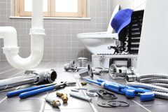 Plumber tools and equipment in a bathroom, plumbing repair service, assemble and install concept royalty free stock photos