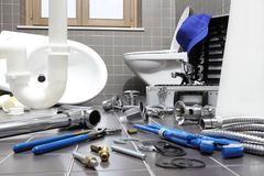 Plumber tools and equipment in a bathroom, plumbing repair service, assemble and install concept stock image