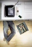 Plumber under kitchen sink Stock Image