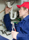 Plumber in uniform repairing pipeline Stock Images