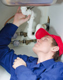 Plumber in uniform repairing pipeline Stock Photography