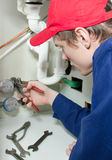 Plumber in uniform repairing pipeline Royalty Free Stock Photo