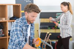Plumber using hacksaw to cut down pipes. Plumber using a hacksaw to cut down some pipes Stock Photography