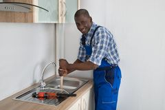 Plumber Using Plunger In Kitchen Sink. Young Happy African Plumber Using Plunger To Unclog Kitchen Sink royalty free stock image