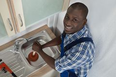 Plumber Using Plunger In Kitchen Sink. Young Happy African Plumber Using Plunger To Unclog Kitchen Sink royalty free stock photography