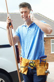 Plumber With Van Talking On Mobile Phone Outside House Stock Image