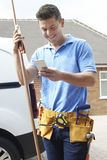 Plumber With Van Texting On Mobile Phone Outside House Royalty Free Stock Photography
