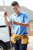 Plumber With Van Texting On Mobile Phone Outside House Royalty Free Stock Photos