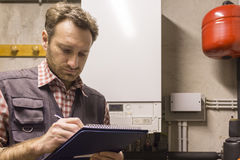 Plumber who carries out the maintenance of a condensing boiler Stock Images